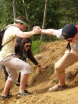 After investigating the growing coffee plants, students work together to climb back up the steep dirt hill.